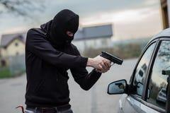 Biltjuv som pekar ett vapen på chauffören Royaltyfri Bild