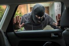 Biltjuv som ser till och med bilfönster arkivfoto