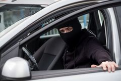 Biltjuven får in i en stulen bil royaltyfri bild