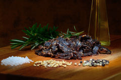 Biltong. A heap of biltong with pepper corns, coriander, salt, rosemary and oil Stock Image