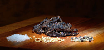 Biltong. A heap of biltong with pepper corns, coriander and salt Royalty Free Stock Images