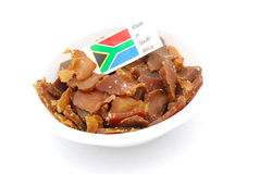 Biltong - South Africa. A bowl of traditonal South African Biltong, a cultural snack of raw dried meat cut into slices with little flag on top. Image isolated on Royalty Free Stock Images