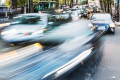 Biltrafik på en parisisk gata i rörelsesuddighet Arkivbilder