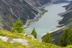 Biltunnel på banken av Livigno sjön i fjällängar, Ital Royaltyfri Bild