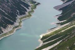 Biltunnel på banken av Livigno sjön i fjällängar, Ital Arkivbild