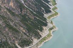 Biltunnel på banken av Livigno sjön i fjällängar, Ital Royaltyfria Bilder