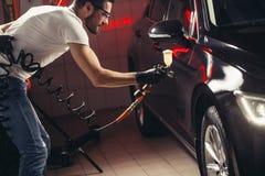 Biltvätt- och beläggningsaffär med den keramiska beläggningen Bespruta fernissa till bilen royaltyfri foto
