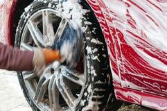 Biltvättarbetare som gör ren bilar arkivbild