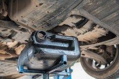 Bilunderhåll som servar mekanikern som häller det nya olje- smörjmedlet in i bilmotorn Arkivfoton