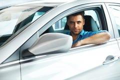 Bilvisningslokal Lycklig man inom bilen av hans dröm Royaltyfri Bild