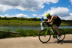Bilzen thriathlon on a sunny Sunday afternoon, with a panning images of amazing athletes. Lanaken, Belgium 05/12/2019 panning photograph of a cycle racer along stock photography
