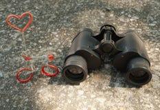 Binóculos da mão e figura da bicicleta com conceito do amor Foto de Stock Royalty Free
