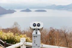 Binóculos a fichas no lago Toya para ver o detalhe de montanha e no lago no Hokkaido, Japão Fotografia de Stock Royalty Free