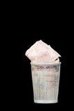 Bin full of Cash. Small wastepaper bin stuffed full of banknotes stock images
