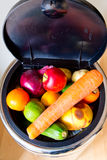 Bin and lid full of fruit and vegetables Royalty Free Stock Photos