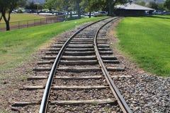 Binari ferroviari che curvano nei più vecchi legami stagionati del parco che entrano nella distanza Immagine Stock Libera da Diritti