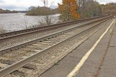 Binari ferroviari lungo la banca di un fiume Immagine Stock