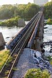 Binari ferroviari sopra un fiume infuriantesi immagine stock