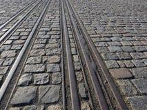 Binari ferroviari sulla pavimentazione del ciottolo fotografia stock