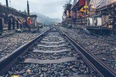 Binario che si dirige fuori dalla stazione ferroviaria alla montagna nebbiosa, tra Immagini Stock