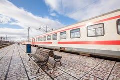 Binario con il banco e treno alla stazione Immagini Stock