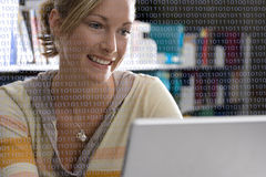 Binary code covering woman using laptop stock photo