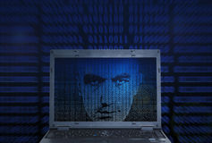 Binary code hacker. Hacker's face appears on laptop screen in binary code Royalty Free Stock Photography