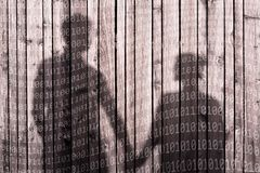 Binary code numbers with couple holdings hands. Shadow of couple on wooden boards wall background holding hands. Abstract binary numbers added. Red color tone royalty free stock photo