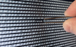 Binary Code. Ransom-DDoS Virus caught by tweezers Royalty Free Stock Photography