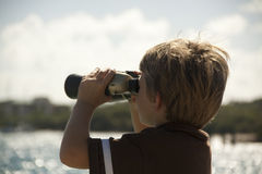 Binauculars. A young boy looking at the sea with his binauculars Stock Photos