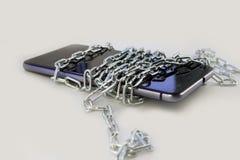 Bind de telefoon met een metaalketting Lichtgrijze achtergrond Geïsoleerd niet royalty-vrije stock afbeelding