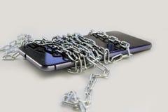 Bind de telefoon met een metaalketting Lichtgrijze achtergrond Geïsoleerd niet stock afbeeldingen