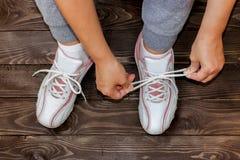 Binda skon snör åt flickasammanträde på trägolvet Vit gymnastiksko royaltyfria bilder