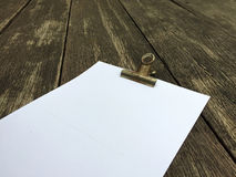 Binder Clip and Stack of Papers on Wooden Background Royalty Free Stock Image