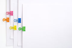 Binder clips. Fasten the white papers together with five colors binder clips Royalty Free Stock Image
