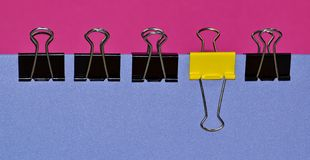Binder clips in a row showing contrast. A side view of a line of black binder clips with a single yellow one to add contrast,  with a backdrop of bold pink and Royalty Free Stock Images