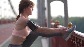 Binder den höga kvinnan för closeupen skosnöret på bron stock video