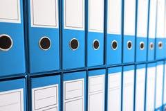 Binder folders in shelf, binders in a row. Royalty Free Stock Image