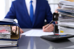 Binders with papers are waiting to be processed with businessman and secretary back in blur. Accounting planning budget. Audit, insurance and business concept Royalty Free Stock Photos