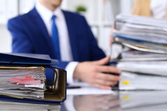 Binders with papers are waiting to be processed with businessman and secretary back in blur. Accounting planning budget Stock Photo