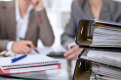 Binders with papers are waiting to be processed with businessman and secretary back in blur. Internal Revenue Service Royalty Free Stock Image