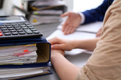 Binders with papers are waiting to be processed with businessman and secretary back in blur. Internal Revenue Service Stock Image