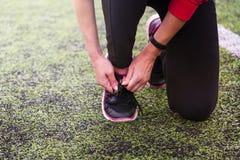 Bindungsspitze des Mädchens Handauf Sportschuhen am Sportstadion stockbild