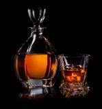 Binge on black. Decanter and glass of whiskaey on black background stock photo
