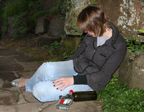 Binge Drinking. A young woman in blue jeans and black jacket sits against a wall in a shadowy parkland setting in a drunk state with alcohol bottles lying on the royalty free stock image