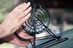Bingo! Eine Nahaufnahme von Händen mit Bingo-Rad und Bällen Stockbilder