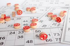 Bingo lub loteryjki gra Drewniane bary?ki loteryjka na kartach Karty i uk?ady scaleni dla bawi? si? bingo na bia?ym stole zdjęcie stock