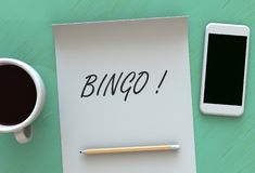 Bingo, message on paper, smart phone and coffee on table. 3D rendering royalty free stock photo