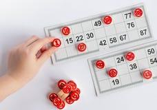 Bingo oder Lottospiel H?lzerne F?sser des Lottos auf Karten Karten und Chips f?r das Spielen von Bingo auf einer wei?en Tabelle lizenzfreie stockbilder