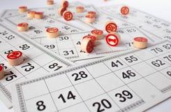 Bingo ou jogo do loto Barris de madeira do loto em cart?es Cart?es e microplaquetas para jogar o bingo em uma tabela branca fotos de stock royalty free